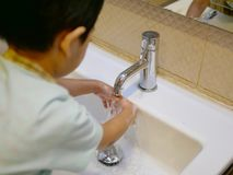 Selective focus of little Asian baby`s hands being wash at a bat royalty free stock photography