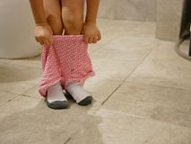 Selective focus of little baby`s short pants being pulled up by herself after the baby finished using a toilet - potty trainning royalty free stock photo