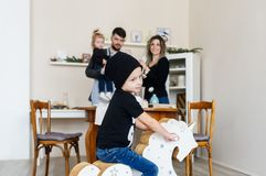 Selective focus of little boy in black cap on wooden horse toy and family at a background royalty free stock photo