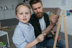 Selective focus of little boy and father with pieces of chalk drawing picture on blackboard. At home royalty free stock photography