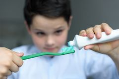 selective focus of little boy putting tooth paste on tooth brush in hand royalty free stock photo