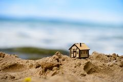 Selective focus on little house. Selective focus on little wooden house in the sand. Symbol of home and movement stock image