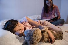 Selective focus of little kid with teddy bear sleeping while mother working. Near by stock image