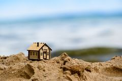 Selective focus on little house. Selective focus on little wooden house in the sand. Symbol of home and movement royalty free stock photography
