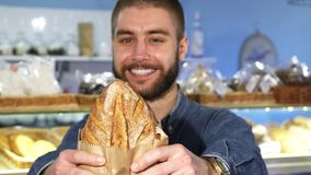 Happy handsome bearded man posing with freshly baked bread. Selective focus on a loaf of delicious bread handsome young man is holding after shopping at the stock video