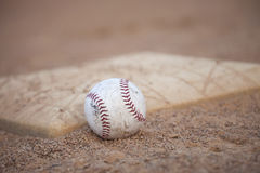 Selective focus low angle of grungy baseball and base Stock Image