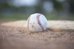 Selective focus low angle of grungy baseball and base Stock Images