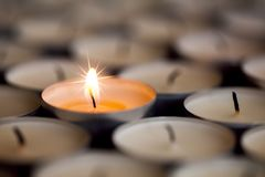 Selective focus on magical light from a single sparkling flame f. Selective focus on shining magical light of a single sparkling flame from one candle among many Stock Photography