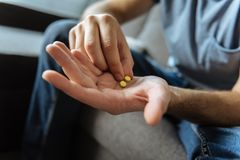 Selective focus of a male palm with pills. My medicine. Selective focus of a palm of a cheerless ill man with two yellow pills Royalty Free Stock Images