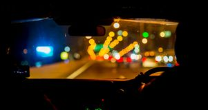 Selective focus of man driving a car at night royalty free stock image