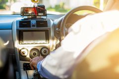 Selective focus of man driving and change gear a car. View from inside the taxi car stock image