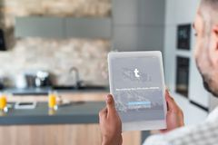 Selective focus of man using digital tablet with twitter logo on screen. In kitchen royalty free stock photo