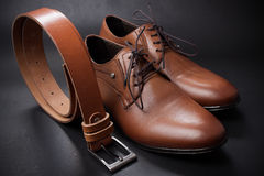 Selective focus of men's leather belt and shoe on wooden table Stock Images