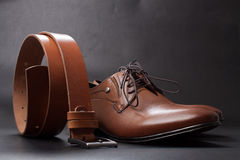Selective focus of men's leather belt and shoe on wooden table Royalty Free Stock Photo