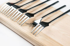 Selective focus on metal shiny forks lined on the wooden board over white background Stock Images