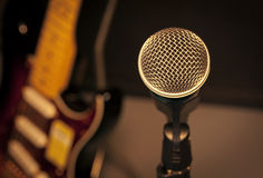 selective focus microphone and blur electric guitar background a Royalty Free Stock Photography