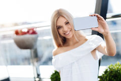Selective focus of a modern innovative smartphone. Modern device. Selective focus of a modern innovative smartphone being used for taking a selfie by a nice Royalty Free Stock Images