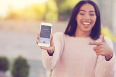 Selective focus of a modern innovative smartphone. Modern app. Selective focus of a modern smartphone being in hands of a pleasant delighted young woman while Stock Images