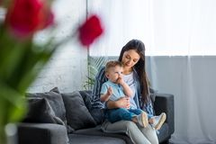 Selective focus of mother with adorable baby boy. On hands sitting on sofa at home stock photos