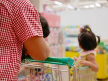 Mother doing shopping, pushing a shopping cart, with her two little daughters inside royalty free stock photography