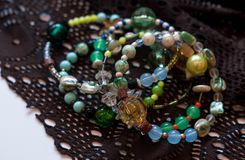 Multicolored bracelets with diferent beads on brown vintage lace on white surface stock image