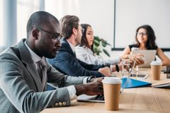 Selective focus of multicultural business people having business meeting. In office stock photos