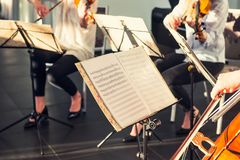 Selective Focus on Music note sheets on stand with background of playing cellists and violinists band on event in bright day sunli. Ght. Commercial music Royalty Free Stock Image