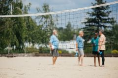 Selective focus of net and interracial old men with volleyball ball. On sandy beach royalty free stock photography
