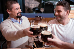 Selective focus of nice cheerful men looking at each other. Drinking beer. Selective focus of nice cheerful handsome men holding glasses with beer and cheering stock photography