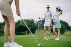 Free Selective Focus Of Smiling Women In Caps With Golf Equipment Looking At Friend Playing Golf Royalty Free Stock Photography - 129002627