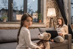 Free Selective Focus Of Upset Kid With Teddy Bear Looking At Camera While Mother Working On Laptop On Sofa Stock Images - 129229654