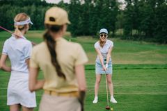 Free Selective Focus Of Women In Caps With Golf Equipment Looking At Friend Playing Golf Stock Images - 129002544