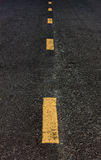 Selective focus old yellow line on road background. Stock Photos