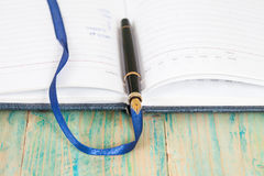 Selective focus of the  pen on opened lined diary book Royalty Free Stock Photography