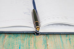 Selective focus of the  pen on opened lined diary book Stock Photos