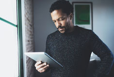 Selective focus.Pensive bearded African man using tablet while standing near the window in his modern apartment.Concept. Of young business people working at Royalty Free Stock Photography