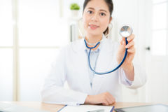 Selective focus photo of beautiful sweet doctor. In blur background and using stethoscope touch screen showing healthy care concept Royalty Free Stock Image