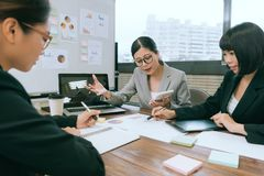 Selective focus photo of company manager lady. Holding calculator reporting company planning during meeting with young business employee royalty free stock photo