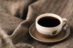 Selective focus photo of cozy knitted scarf with to cup of coffe. E and open book. style retro filtered Stock Images