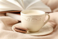 Selective focus photo of cozy knitted scarf with to cup of coffe. E and open book. style retro filtered Stock Photography