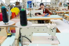 Studio clothing sewing factory tailor machine. Selective focus photo of fashion studio clothing sewing factory tailor machine with blur female worker employee in stock images