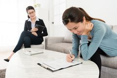 Selective focus photo of girl signing document. Selective focus photo of smiling pretty girl signing document to buy family insurance when business agent women Royalty Free Stock Photography