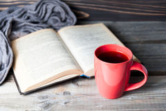 Selective focus photo of grey cozy knitted scarf with cup of coffee or tea and open book on a wooden table. Stock Photo