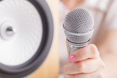 Selective focus photo of microphone in human hand Royalty Free Stock Photo