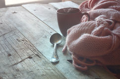 Selective focus photo of pink cozy knitted scarf with to cup of coffee  Royalty Free Stock Photo