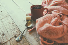 Selective focus photo of pink cozy knitted scarf with to cup of coffee on a wooden table. workspace or coffee break Royalty Free Stock Image