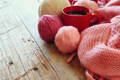Selective focus photo of pink cozy knitted scarf with to cup of coffee and wool yarn balls on a wooden table Royalty Free Stock Photo