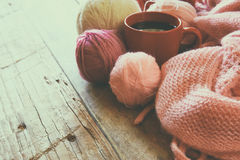 Selective focus photo of pink cozy knitted scarf with to cup of coffee and wool yarn balls on a wooden table Royalty Free Stock Images