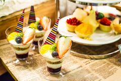 Selective focus photo of Seasonal Tropical Fruit creamy trifle in beautiful glasses with fresh ripe fruit slice, table background. Selective focus photo of Stock Photo