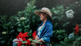 Selective Focus Photo of Woman in Blue Shawl and Brown Sun Hat in the Middle of Garden royalty free stock photo